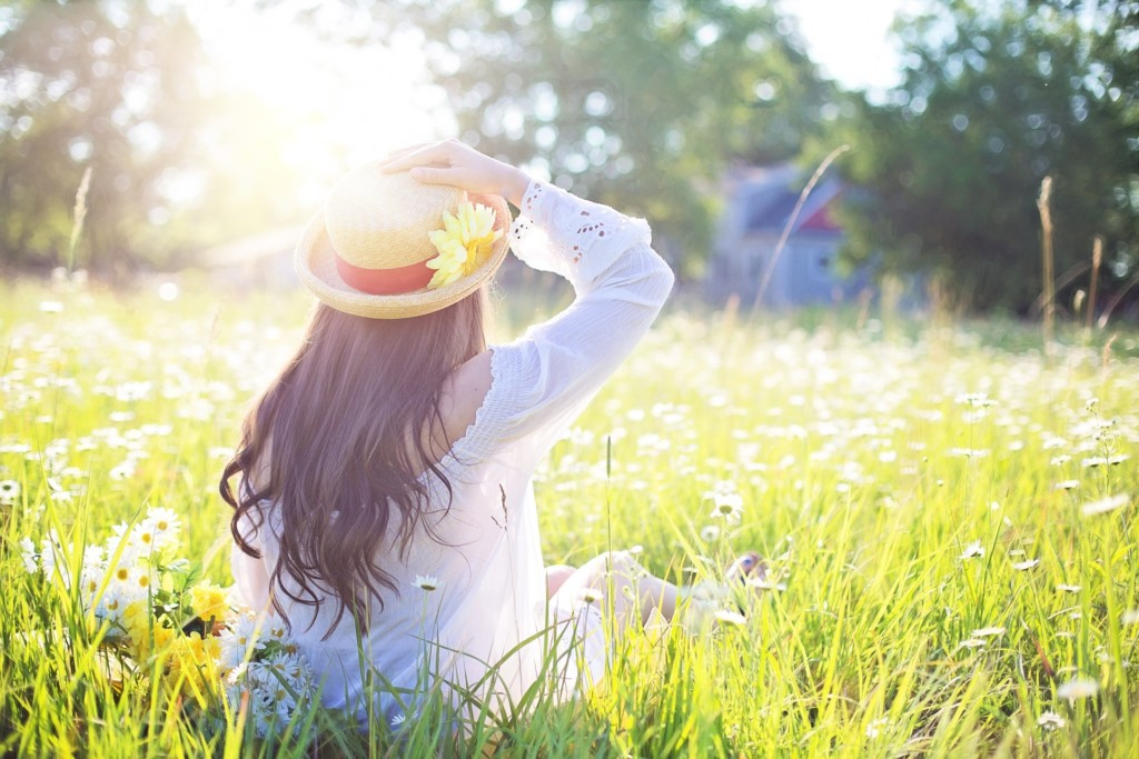 woman in a meadow with a sunflower on her hat